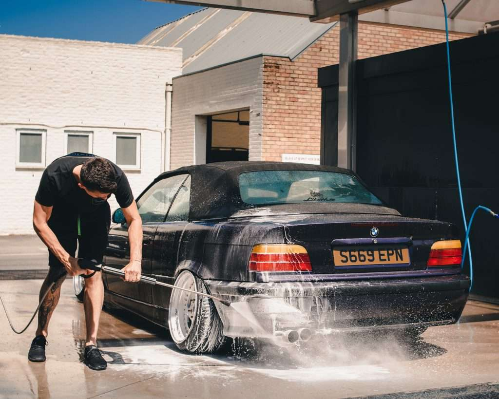Man cleaning his car as part of regular car maintenance.