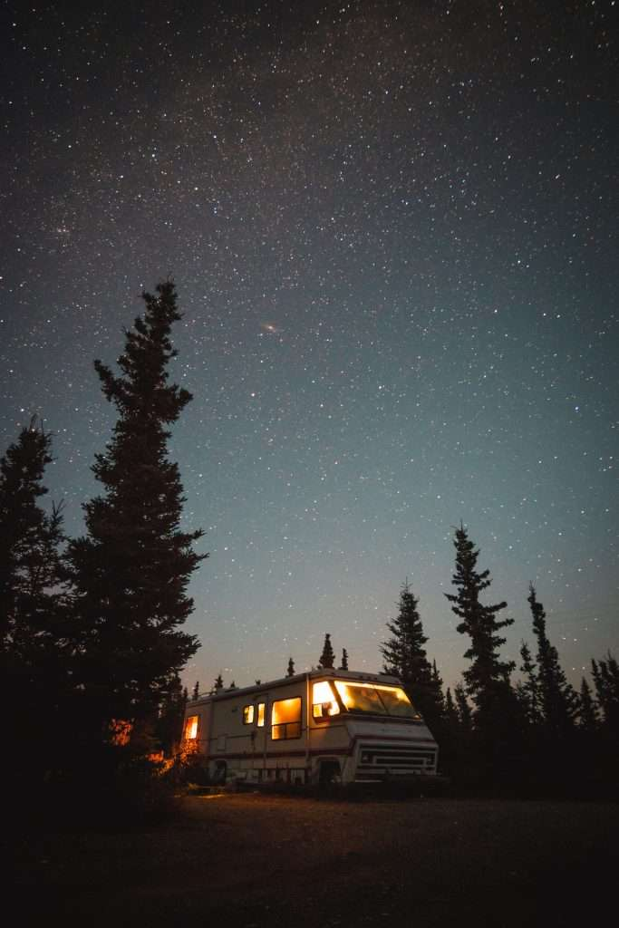 RV Camper lit up with solar power at night in the forest